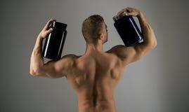 Eet een gezonde voeding Sterke het supplementflessen van de mensengreep Spiermens met vitaminesupplementen Bodybuildingssport en stock foto