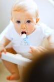Eet gesmeerde baby in stoel het voeden door moeder Stock Foto's