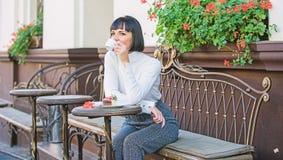 Eet het het gezichts dromerige brunette van de vrouwenmake-up het terrasachtergrond van de cakekoffie Gastronomisch plezier Gastr stock afbeeldingen