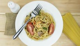 Eet lunchspaghetti in een de decoratievork van schotel witte steunen en Ruwe Spaghettilijnen op witte houten vloerachtergrond stock fotografie