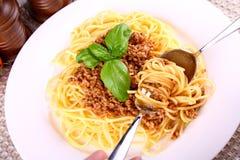 Eet spaghetti bolognese met lepel en vork stock afbeeldingen