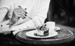 eetlustconcept De kop van de dessertcake van koffie en vrouwelijke hand met vork dichte omhooggaand Stuk van cake met rode bes ga royalty-vrije stock afbeelding