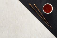 Eetstokjes en kom met saus op lijstmat royalty-vrije stock afbeeldingen
