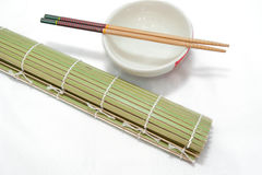 Eetstokjes en kom op bamboemat, Geïsoleerde witte achtergrond royalty-vrije stock fotografie