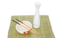 Eetstokjes en kom op bamboemat, Geïsoleerde witte achtergrond stock foto's