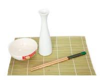 Eetstokjes en kom op bamboemat, Geïsoleerde witte achtergrond stock foto