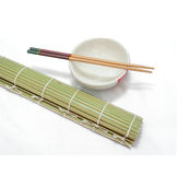 Eetstokjes en kom op bamboemat, Geïsoleerde witte achtergrond royalty-vrije stock afbeeldingen