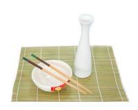 Eetstokjes en kom op bamboemat, Geïsoleerde witte achtergrond royalty-vrije stock foto