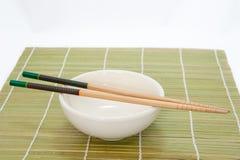 Eetstokjes en kom op bamboemat, witte achtergrond royalty-vrije stock afbeelding