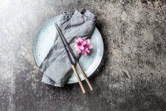 Eetstokjes en sakurabloemen op grijze plaat, steenachtergrond Japans voedselconcept Hoogste mening, exemplaarruimte stock foto