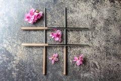 Eetstokjes en sakurabloemen op grijze steenachtergrond Japans voedselconcept Hoogste mening, exemplaarruimte royalty-vrije stock afbeelding