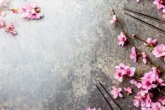 Eetstokjes en sakuratakken op grijze steenachtergrond Japans voedselconcept Hoogste mening, exemplaarruimte stock foto