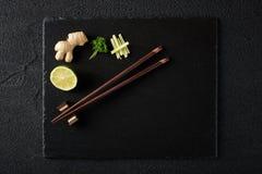 Eetstokjes en voedselingrediënten op zwarte steenlijst royalty-vrije stock foto