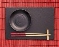 Eetstokjes en zwarte plaat op leionderlegger voor glazen op rode bamboerol stock afbeelding