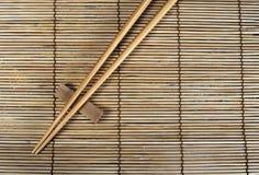 Eetstokjes op bamboemat stock afbeelding