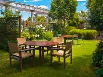 Eettafel die in weelderige tuin wordt geplaatst Royalty-vrije Stock Foto's