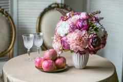 Eettafel met klassieke stoelen, een boeket van hydrangea hortensia en pioenen in een vaas, wijnglazen en appelen stock foto's