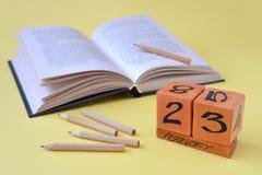 Eeuwige houten kalender met datum van 23 Februari, een geopend boek en potloden op een gele achtergrond met exemplaarruimte stock fotografie