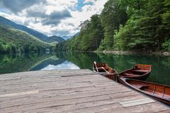 Eevergreen forest on the Biogradskoe lake from wooden pier with rowboat. Biogradska Gora national park. Montenegro, Europa royalty free stock image