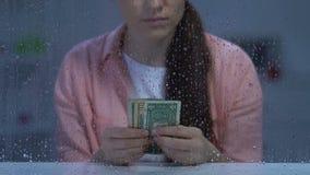 Efectivo de cuenta femenino de mediana edad pobre pensativo del dólar y mirada en ventana lluviosa almacen de metraje de vídeo