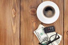 Efectivo del dinero, vidrios, telecontrol del coche y taza de café Imágenes de archivo libres de regalías