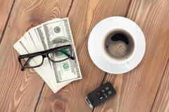 Efectivo del dinero, vidrios, telecontrol del coche y taza de café Fotos de archivo