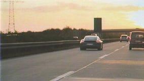 Efecto de la cinta de VHS sobre los coches sobre la carretera alemana del autobahn en la puesta del sol almacen de video