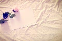 Efecto del estilo del color del vintage: Papeles en blanco/vacíos con la rosa artificial del rosa en una hoja de cama arrugada foto de archivo