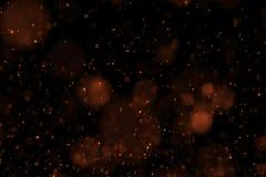 Efecto que fluye del bokeh de las partículas del resplandor del oro sobre el fondo negro, Feliz Año Nuevo del día de fiesta Foto de archivo libre de regalías