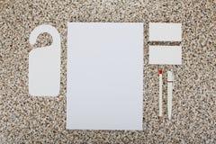 Efectos de escritorio en blanco en el fondo de mármol Consista en las tarjetas de visita, los papeles con membrete A4, la pluma y imagen de archivo libre de regalías