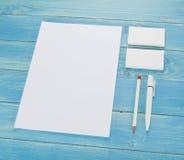 Efectos de escritorio en blanco en fondo de madera Consista en las tarjetas de visita, los papeles con membrete A4, la pluma y el imagen de archivo