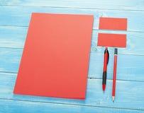 Efectos de escritorio en blanco en fondo de madera Consista en las tarjetas de visita, los papeles con membrete A4, la pluma y el foto de archivo