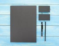 Efectos de escritorio en blanco en fondo de madera Consista en las tarjetas de visita, los papeles con membrete A4, la pluma y el imagenes de archivo