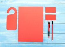 Efectos de escritorio en blanco en fondo de madera Consista en las tarjetas de visita, los papeles con membrete A4, la pluma y el Fotografía de archivo