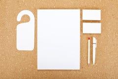 Efectos de escritorio en blanco en tablero del corcho Consista en las tarjetas de visita, los papeles con membrete A4, la pluma y fotos de archivo