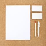 Efectos de escritorio en blanco en tablero del corcho Consista en las tarjetas de visita, los papeles con membrete A4, la pluma y imagenes de archivo