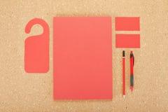 Efectos de escritorio en blanco en tablero del corcho Consista en las tarjetas de visita, los papeles con membrete A4, la pluma y fotografía de archivo libre de regalías