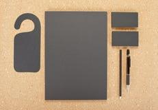 Efectos de escritorio en blanco en tablero del corcho Consista en las tarjetas de visita, los papeles con membrete A4, la pluma y imagen de archivo