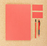 Efectos de escritorio en blanco en tablero del corcho Consista en las tarjetas de visita, los papeles con membrete A4, la pluma y fotos de archivo libres de regalías
