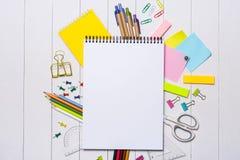 Efectos de escritorio o materiales de oficina de la escuela en el fondo de madera Imágenes de archivo libres de regalías