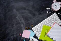 Efectos de escritorio o materiales de oficina de la escuela en fondo de la pizarra Imágenes de archivo libres de regalías