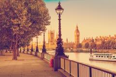 Efeito retro do filtro da foto - lâmpada de rua no banco sul do rio Tamisa com Big Ben e do palácio de Westminster no fundo, Lond imagem de stock