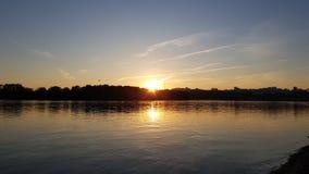 Efeitos do por do sol ou do pôr do sol na superfície da água do lago ou do rio Imagem de Stock Royalty Free
