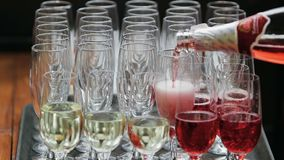 Efervescência do close-up no champanhe Um champanhe vermelho é derramado em um vidro de uma garrafa Champanhe efervescente branco vídeos de arquivo