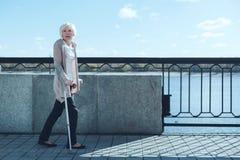 Effacée dame avec des béquilles promenading le long du riverwalk Photographie stock