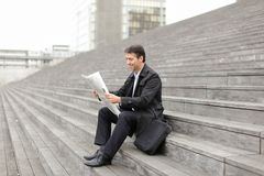 Male business tutor sitting on stairs and reading newspaper. Effect. Tutor dressed in gray coat sitting on rung and read morning newspaper. Articles pleased man Royalty Free Stock Photo