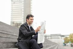 Male business tutor sitting on stairs and reading newspaper. Effect. Tutor dressed in gray coat sitting on rung and read morning newspaper. Articles pleased man Stock Photography