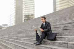 Male business tutor sitting on stairs and reading newspaper. Effect. Tutor dressed in gray coat sitting on rung and read morning newspaper. Articles pleased man Royalty Free Stock Photos