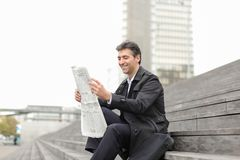 Male business tutor sitting on stairs and reading newspaper. Effect. Tutor dressed in gray coat sitting on rung and read morning newspaper. Articles pleased man Royalty Free Stock Image
