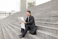 Male business tutor sitting on stairs and reading newspaper. Effect. Tutor dressed in gray coat sitting on rung and read morning newspaper. Articles pleased men Stock Images